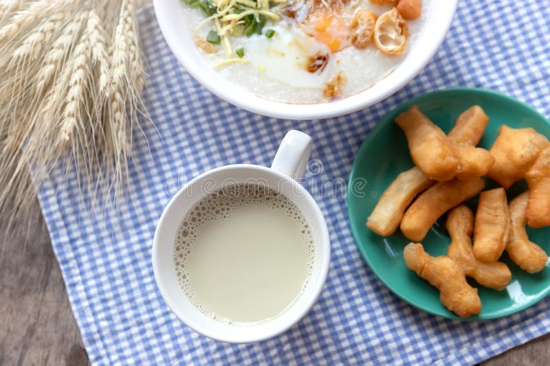 Breakfase meal. Congee or Rice porridge minced pork, boiled egg with soy milk and Chinese deep fried double dough stick.  stock photo