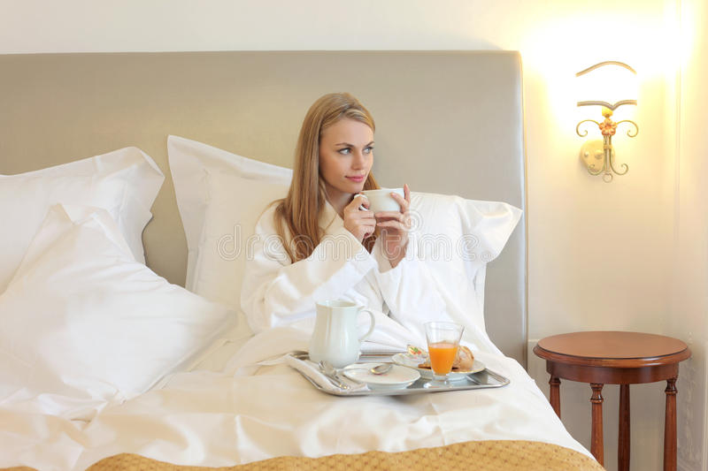 Breakfast. Woman having breakfast at bed royalty free stock images