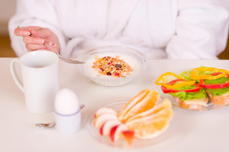 Breakfast. Woman eating breakfast on the morning table royalty free stock images