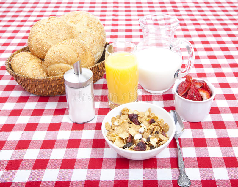 Breakfast. Of cereal, fruit, rolls, orange juice and milk on tablecloth royalty free stock photography