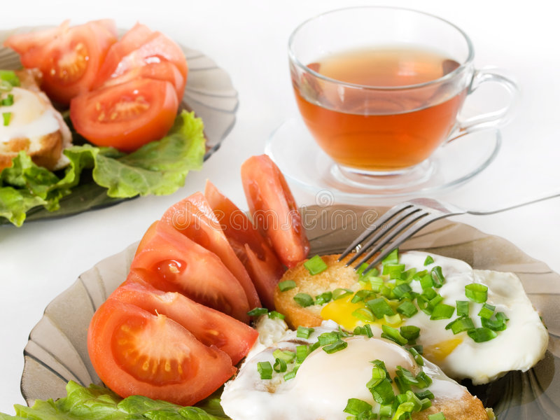 Breakfast. For a family - fried eggs with tomatoes stock photos