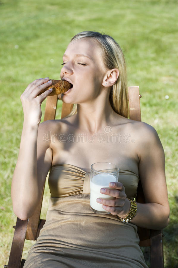 Breakfast. Girl eats the breakfast in the orchard royalty free stock photography