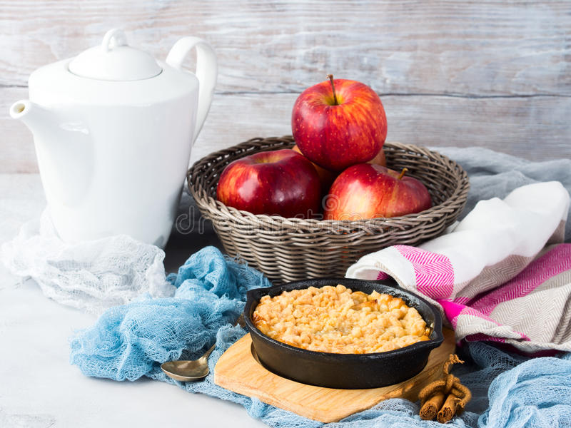 Breakfast with apple crumble in cast iron skillet. Home made apple crumble in cast iron skillet on wooden serving board. Cozy and healthy breakfast set with stock photography