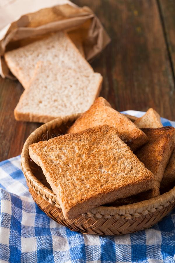 Breakfast background, toasts on checkered napkin closeup. Breakfast background, white bread toasts in wicker breadbasket on checkered table napkin half covering stock photo