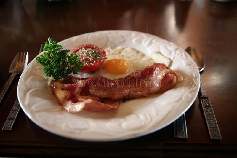 Breakfast of bacon and eggs. Breakfast with bacon and egg accompanied by tomato and coriander royalty free stock image