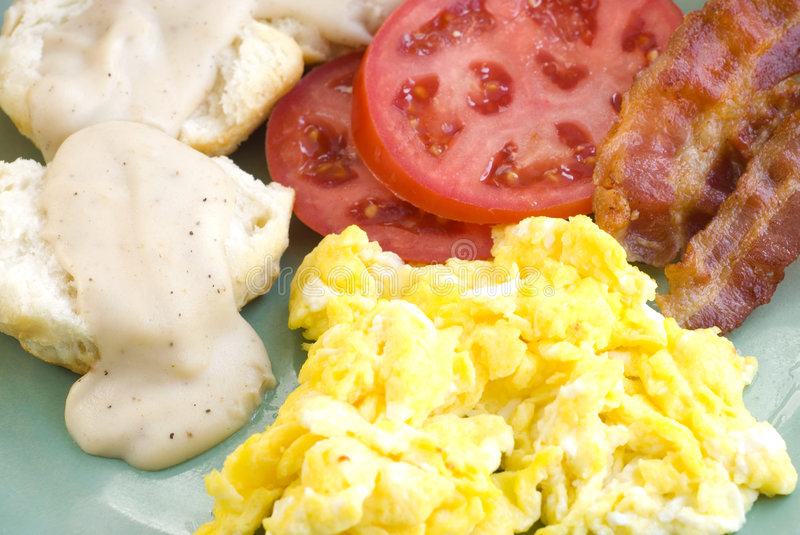Breakfast with bacon and eggs. Country breakfast with crispy bacon stripes, scrambled eggs, milk gravy and buttermilk biscuits, closeup with detail stock images