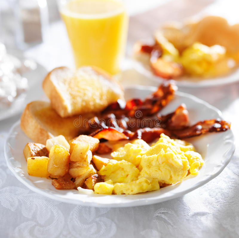 Breakfast with bacon, eggs and home fries. On white tablecloth, shot with selective focus stock photos