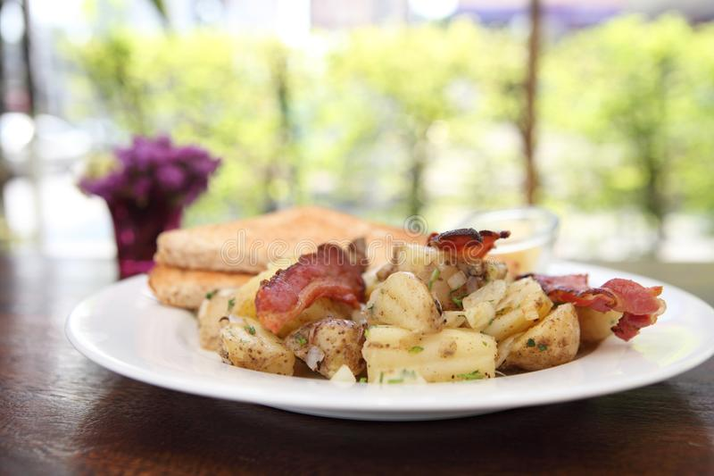 Breakfast of bacon, toast and hash browns royalty free stock photography