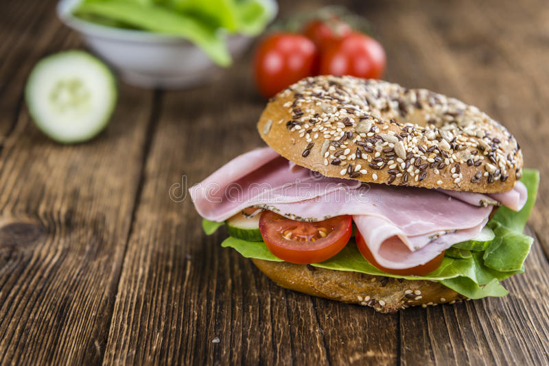 Breakfast Bagel (with ham; selective focus). On vintage looking background stock photo