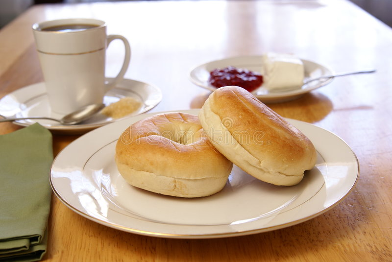 Breakfast Bagels. Breakfast of plain bagels with coffee, cream cheese, and strawberry preserves royalty free stock photo