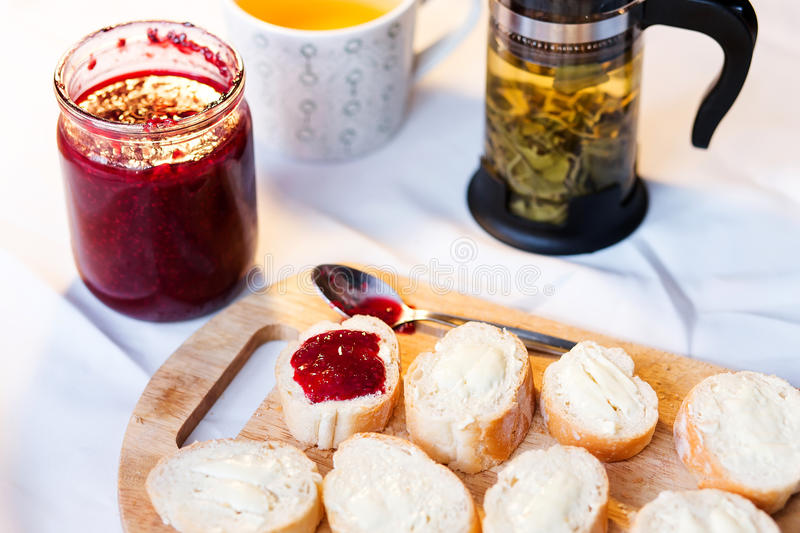 Breakfast with baguette. Butter, jam and tea royalty free stock photo