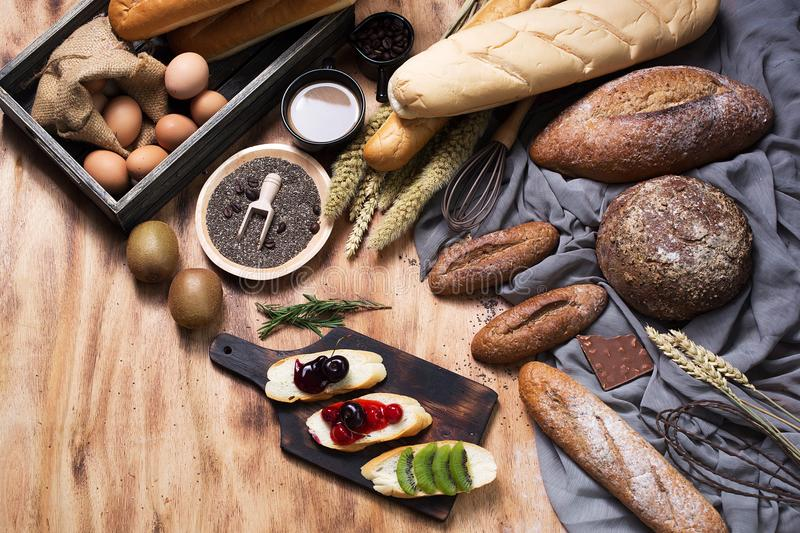 Breakfast and baked bread concept. Fresh fragrant bread and egg. On wooden table. Fresh bread and coffee and wheat on wood black background. Kiwi and chocolate royalty free stock photos