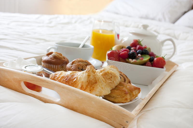 Breakfast in bed. With fruits and pastries on a tray stock images