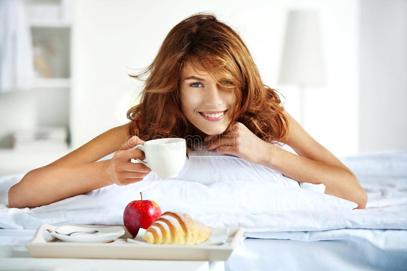 Breakfast in bed. Beautiful brunette woman holding white porcelain cup in hand and smiling lying in bed stock photo