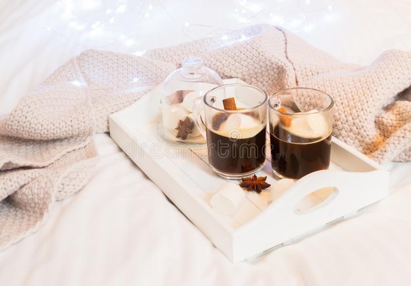 Breakfast in bed. For two - tray with cup of coffee and sweet marshmallows, cozy hygge home style with knitted scarf royalty free stock image