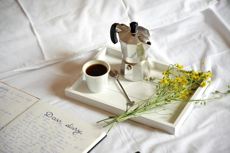 Breakfast in bed with coffee and diary on white sheets. And yellow , spring flowers . romantic breakfast concept image royalty free stock photography