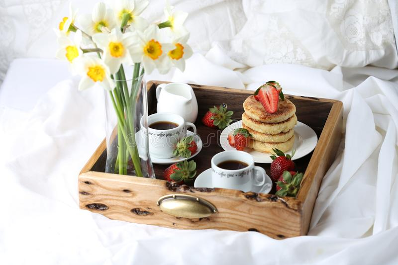 Breakfast in bed: cottage cheese pancakes, coffee and strawberries stock image