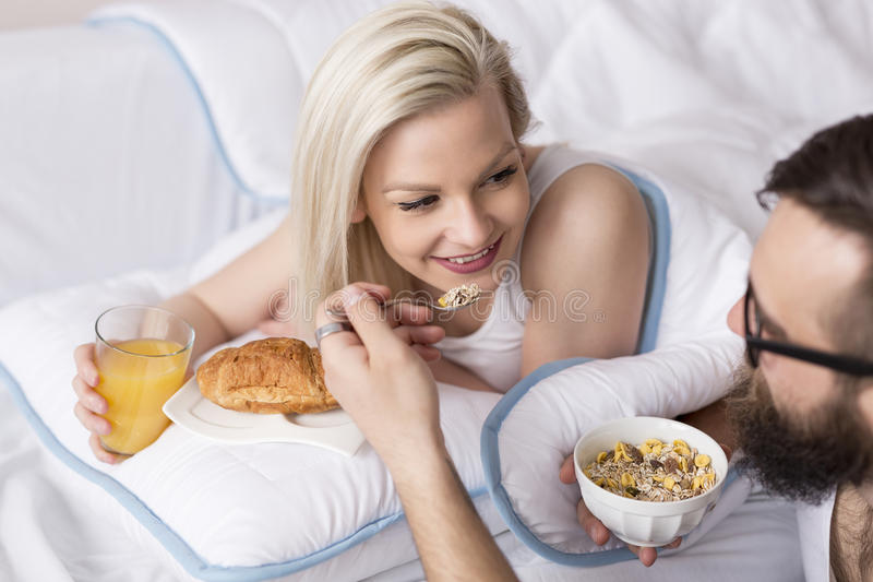 Breakfast in bed. Couple in love wearing pajamas and having a breakfast in bed stock photos