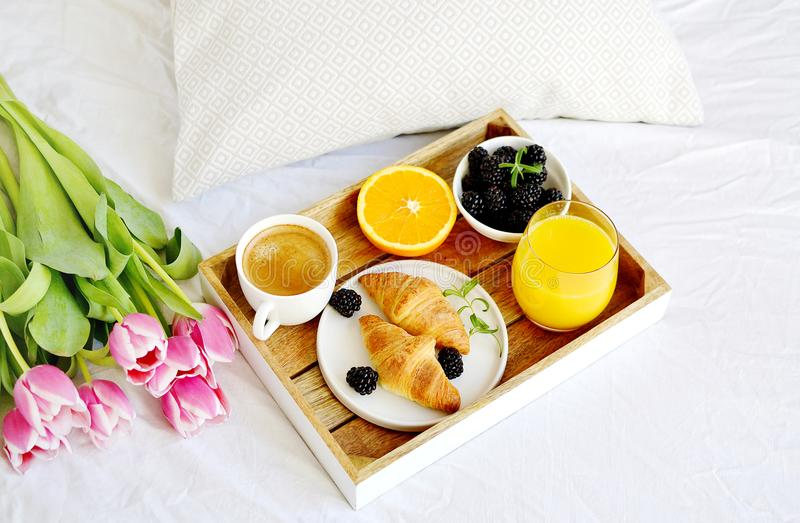 Breakfast in bed, croissant, coffee cup, berries, orange juice, stock images