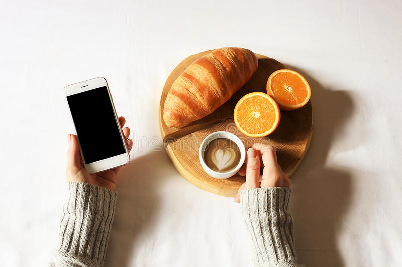 Breakfast in bed flat lay. Woman hands holding cup of coffee and phone, wooden cut with fresh croissant and strawberry in bed. Top. Breakfast in bed flat lay stock image