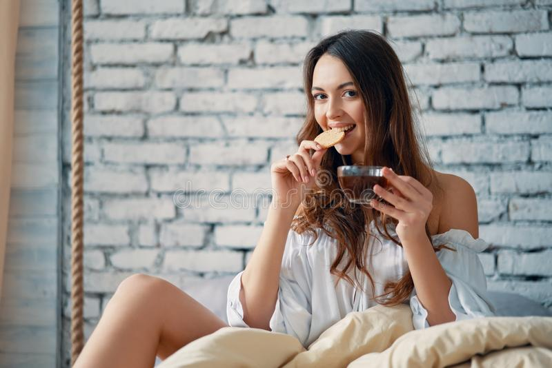 Happy woman enjoy aroma coffee in bed after wake up royalty free stock images
