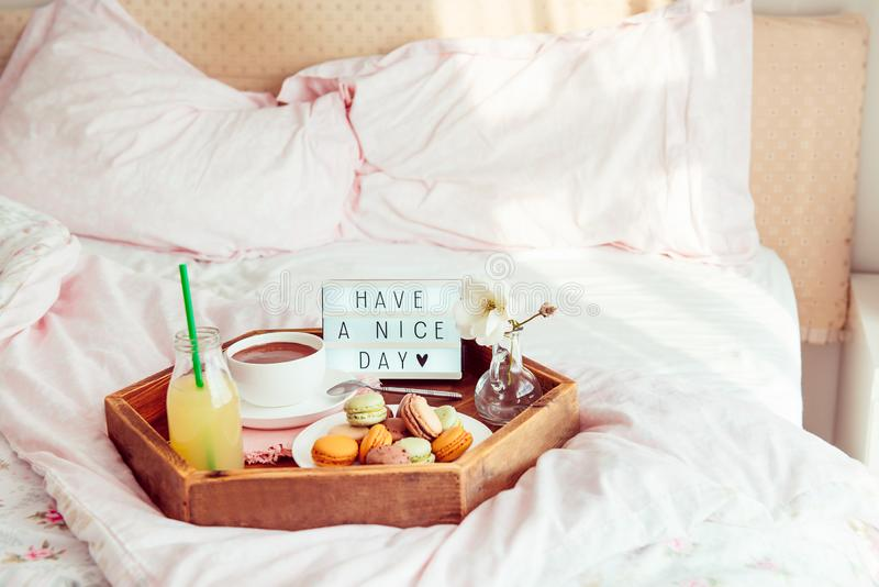 Breakfast in bed with Have a nice day text on lighted box. Cup of coffee, juice, macaroons, flower in vase on wooden tray. Good. Morning mood. Hospitality, care royalty free stock image