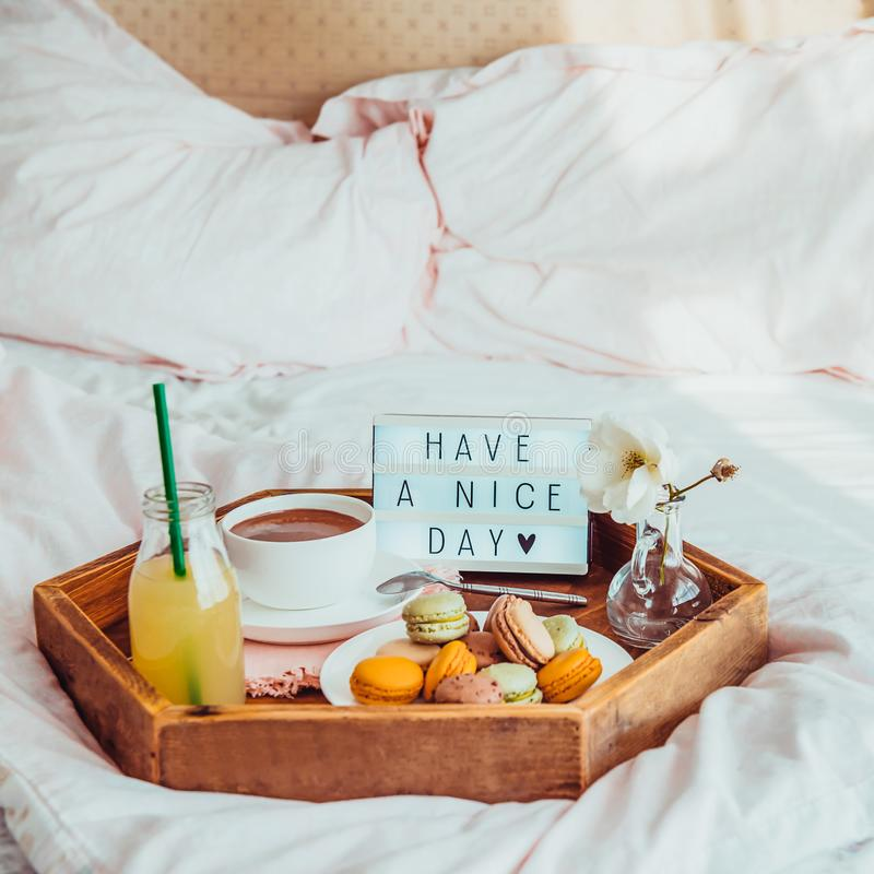 Breakfast in bed with Have a nice day text on lighted box. Cup of coffee, juice, macaroons, flower in vase on wooden tray. Good. Morning mood. Hospitality, care stock photos