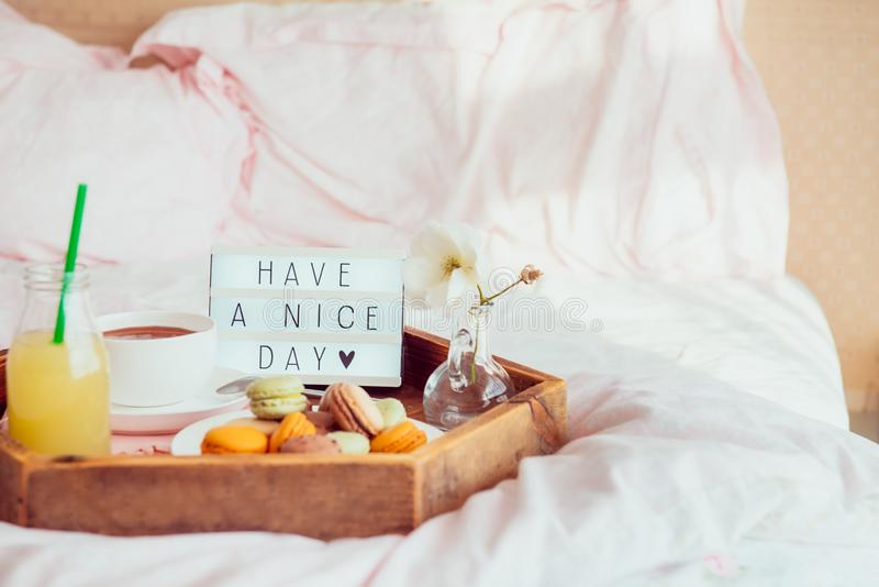 Breakfast in bed with Have a nice day text on lighted box. Cup of coffee, juice, macaroons, flower in vase on wooden tray. Good. Romantic Breakfast in bed with I royalty free stock image