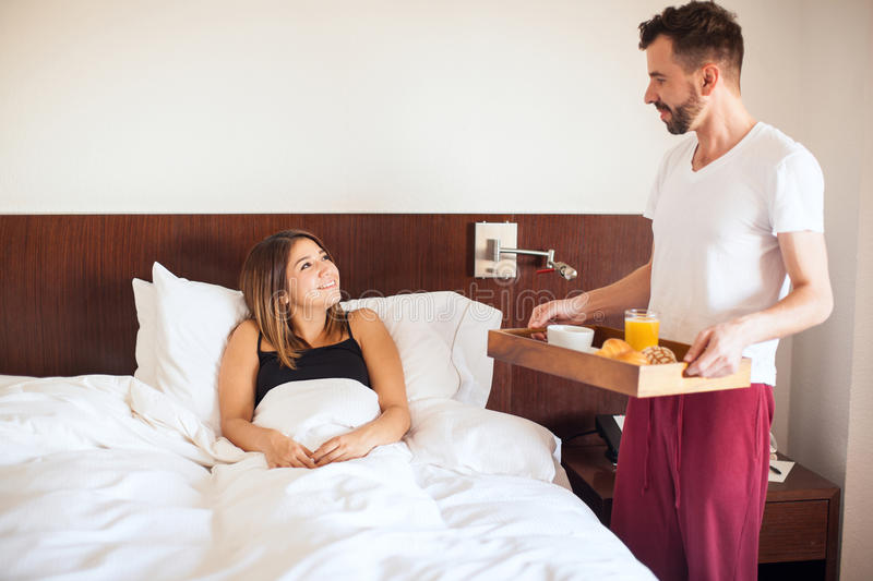 Breakfast in bed at home. Good looking young brunette excited about the breakfast her husband brougth her to bed royalty free stock photo