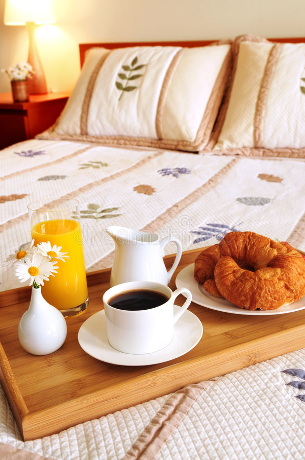 Breakfast on a bed in a hotel room stock photography