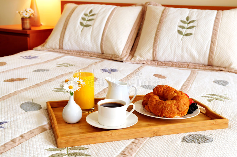 Breakfast on a bed in a hotel room stock photo
