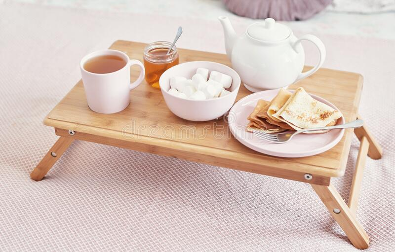 Breakfast in bed in hotel room. Accommodation. Breakfast in bed with tea cup with pancakes on tray on bed background top view. royalty free stock images