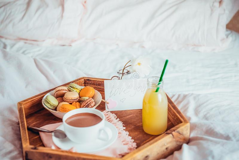 Breakfast in bed with i love you text on a note. Cup of coffee or cocoa, juice, macaroons, rose flower on wooden tray. Romantic stock photography