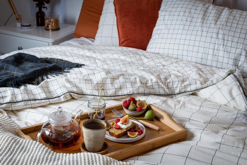 Breakfast in bed with pastry and fresh fruits, black tea royalty free stock images
