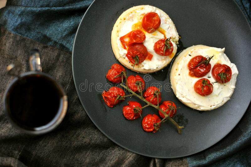 Breakfast in bed with toasted tomatoes on crumpets. Breakfast in bed with grilled tomatoes on crumpets and cheese on a red background. healthy breakfast and slow stock photography