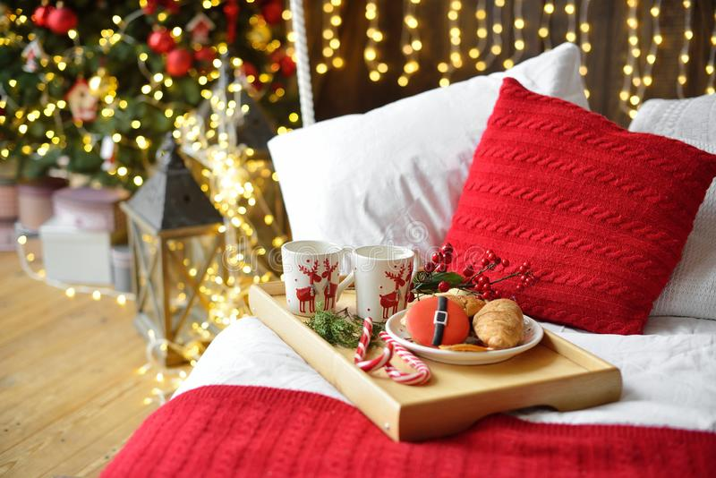 Breakfast in bed, tray with cup of coffee and croissant. Modern bedroom interior. Romantic morning surprise. Christmas mood stock image