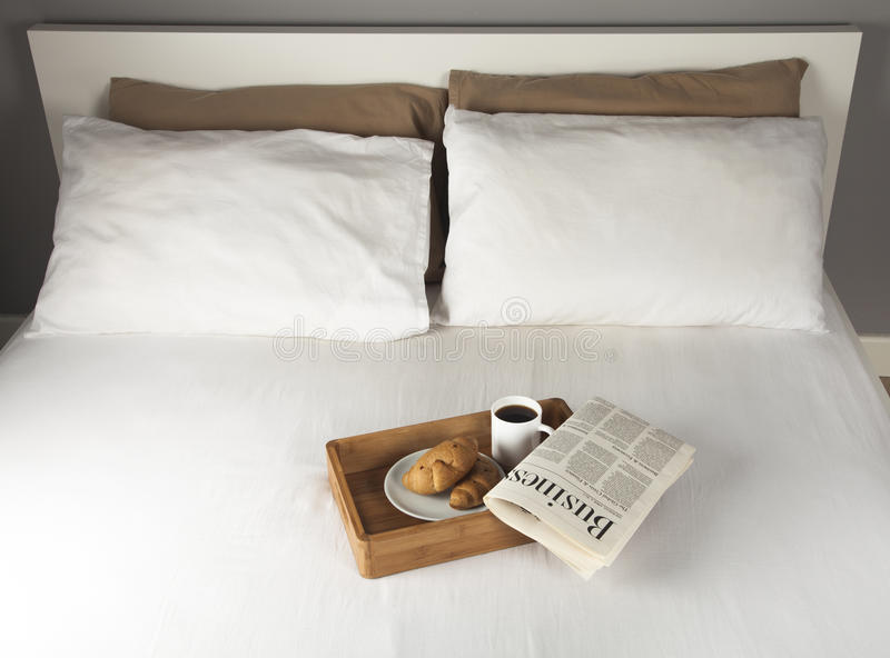 Breakfast on bed. Breakfast tray and newspaper on a bed royalty free stock photos