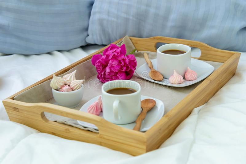 Breakfast in bed for two. Wooden tray with coffee, macaroons and Bizet. Decoration pink peony. Beautiful natural light from the window stock image