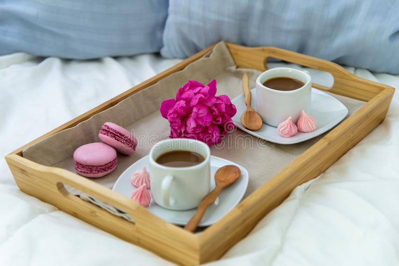 Breakfast in bed for two. Wooden tray with coffee, macaroons and Bizet. Decoration pink peony. Beautiful natural light from the window stock images
