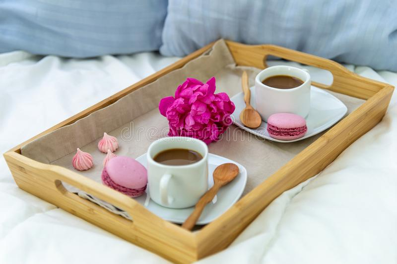 Breakfast in bed for two. Wooden tray with coffee, macaroons and Bizet. Decoration pink peony. Beautiful natural light from the window royalty free stock photo