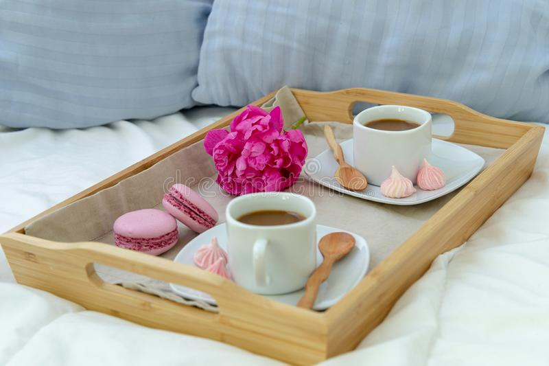 Breakfast in bed for two. Wooden tray with coffee, macaroons and Bizet. Decoration pink peony. Beautiful natural light from the window stock photos
