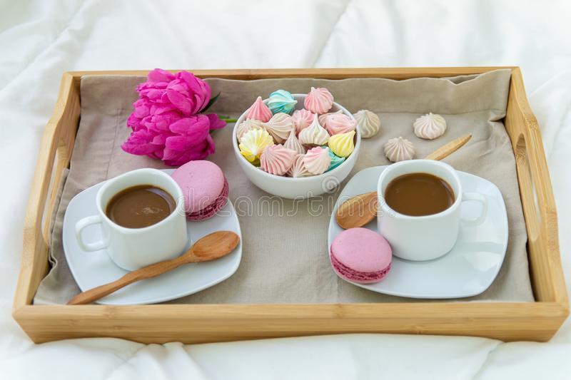 Breakfast in bed for two. Wooden tray with coffee, macaroons and Bizet. D. Ecoration pink peony. Beautiful natural light from the window stock photos