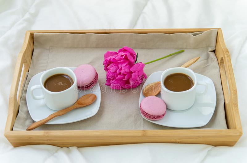 Breakfast in bed for two. Wooden tray with coffee, macaroons and Bizet. Decoration pink peony. Beautiful natural light from the window stock photography