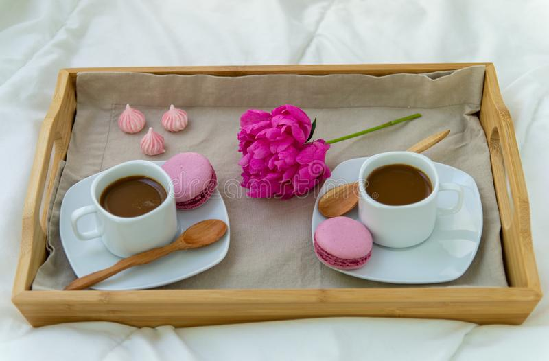 Breakfast in bed for two. Wooden tray with coffee, macaroons and Bizet. Decoration pink peony. Beautiful natural light from the window royalty free stock photography