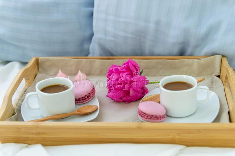 Breakfast in bed for two. Wooden tray with coffee, macaroons and Bizet. Decoration pink peony. Beautiful natural light from the window royalty free stock photos