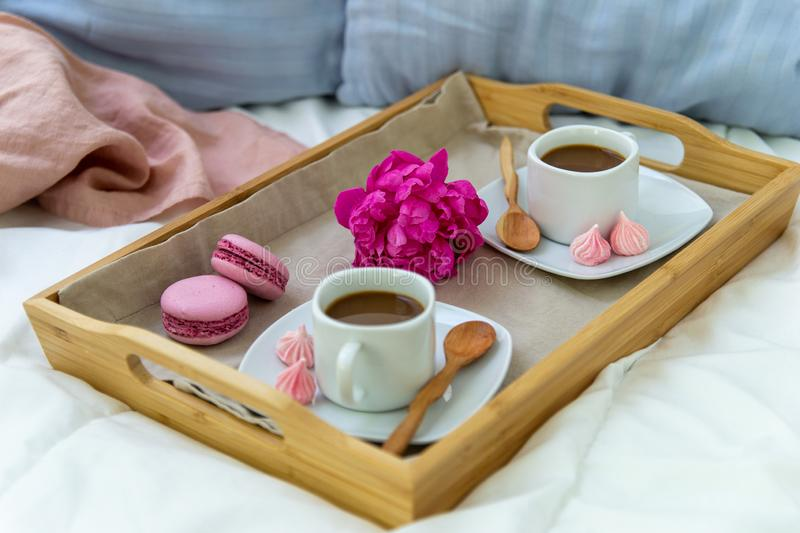 Breakfast in bed for two. Wooden tray with coffee, macaroons and Bizet. Decoration pink peony. Beautiful natural light from the window royalty free stock image