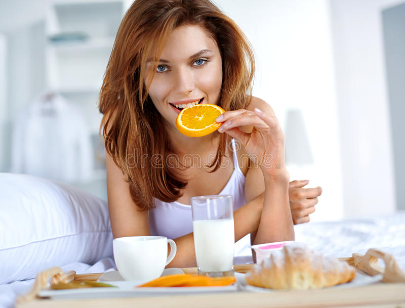 Breakfast in bed. Woman eating healthy fruit in bed while happy and smiling royalty free stock images
