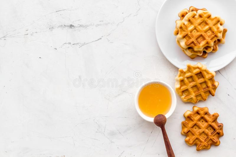 Breakfast with Belgian waffles with honey and spoon on white marble background top view mock up. Homemade bakery. Breakfast with Belgian waffles with honey and royalty free stock image