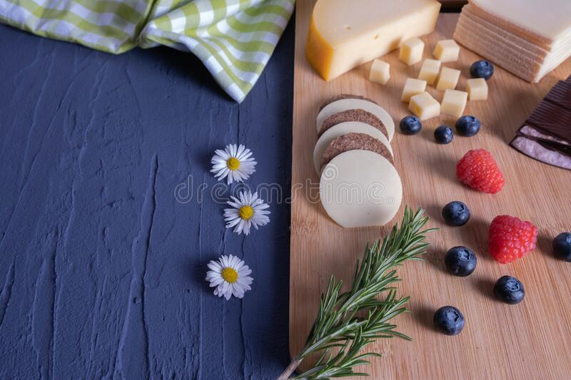 Breakfast with berries, chocolate and chopped cheese. On a wooden board stock image