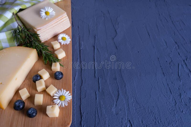 Breakfast with berries, daisies and chopped cheese. On a wooden board stock image